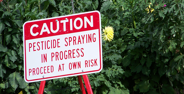 "Sign warning ""Pesticide Spraying in Progress: Proceed at Your Own Risk"""